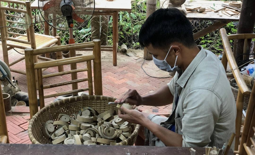 Mann bearbeitet Holzstücke in Hoi An-min